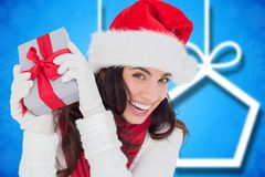 Excited woman in santa hat holding her christmas gift Royalty Free Stock Photo