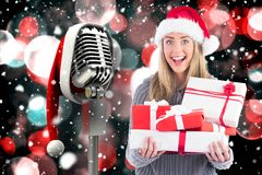 Excited woman in santa hat holding stack of gifts Royalty Free Stock Photos