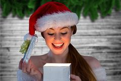 Excited woman in santa hat opening christmas gift Royalty Free Stock Photos