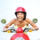 Excited woman on scooter happy. Funny portrait of woman driving scooter wearing red helmet. Beautiful mixed race Caucasian / Asian Chinese girl Royalty Free Stock Photos