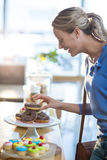 Excited woman selecting doughnuts from cake stand Royalty Free Stock Photo