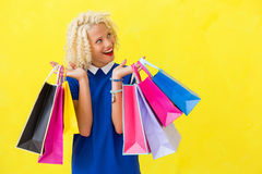 Excited woman with shopping bags looking up Stock Photo