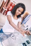 Excited woman shopping in jewelry store. Casual ethnic woman trying stylish ring in bijouterie shop and looking excited Royalty Free Stock Photos