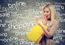 Excited woman shopping online checking prices on mobile phone. Surprised girl with colorful bags looking at cellphone Royalty Free Stock Photo
