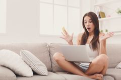Excited woman shopping online with credit card. And laptop, sitting on couch, copy space Royalty Free Stock Photography