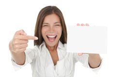 Excited woman showing blank sign. Woman pointing excited at blank card sign with copy space. Woman in white shirt isolated on white background Stock Images