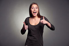 Excited woman showing thumbs up. Happy excited woman showing thumbs up over dark background Royalty Free Stock Photos