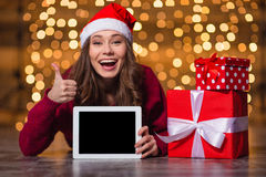 Excited woman showing thumbs up and holding tablet blank screen Royalty Free Stock Images