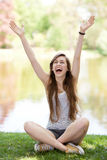 Excited woman sitting with arms raised Royalty Free Stock Photo