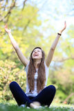 Excited woman sitting with arms raised Royalty Free Stock Photos