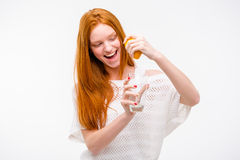 Excited woman squeezing orange juice into a glass by hand Stock Photography