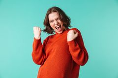 Excited woman standing isolated make winner gesture. Photo of excited woman standing isolated over blue background looking camera make winner gesture Royalty Free Stock Photos