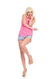 Excited woman standing on one leg and pointing Royalty Free Stock Images