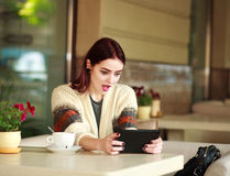 Excited woman in summer cafe looking at tablet Royalty Free Stock Photos