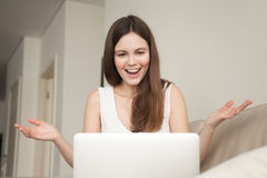 Excited woman surprisingly looking at laptop amazed by good news. Excited woman surprisingly looking at laptop, raising hands amazed by good news while sitting Stock Photography