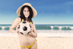 Excited woman in swimsuit holding soccer ball 1. Portrait of sexy woman wearing bikini holding a soccer ball on beach Royalty Free Stock Photography