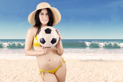 Excited woman in swimsuit holding soccer ball. Portrait of sexy woman wearing bikini holding a soccer ball on beach Stock Photo