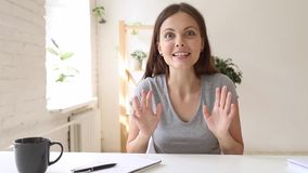 Excited woman telling news to friend looking at webcam. Overjoyed woman sitting indoors wave hand greeting associate telling unbelievable news to friend looking stock video footage