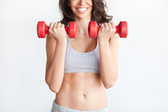 Excited woman training biceps with dumbbells Royalty Free Stock Image