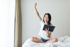 Excited Woman using digital tablet at home Stock Photos