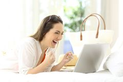 Excited woman using a laptop in vacations. Excited woman using a laptop lying on a bed in an hotel room on summer vacations Stock Photos