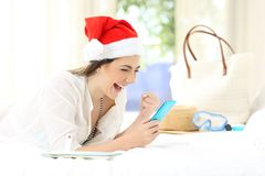Excited woman using a phone on christmas holidays. Lying on a bed in an hotel room stock images