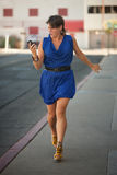 Excited woman walks and calls on cell phone. Stock Images