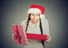 Excited woman wearing red santa claus hat opening gift box. Young excited woman wearing red santa claus hat, opening gift box isolated on gray background stock photography