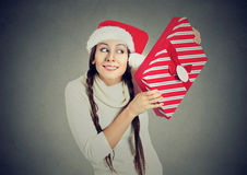 Excited woman wearing santa claus hat opening gift box. Young excited woman wearing red santa claus hat, opening gift box isolated on gray background. Positive royalty free stock photos