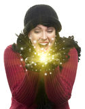 Excited Woman In Winter Clothes Holds Something Sparkling In Han. Excited Woman Wearing Winter Hat, Scarf and Gloves Holds Something Magical and Sparkling in the royalty free stock images