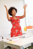 Excited Woman Working At Desk In Design Studio Stock Photography