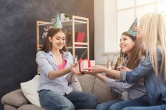 Excited woman getting gift from her friends. Excited women in birthday cap getting present from her friends. Birthday, holidays, celebration and female Stock Images