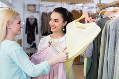 Excited women choosing pullover and skirt Stock Photography