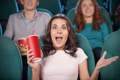 Excited women at the cinema. Beautiful young women drinking soda and gesturing while watching movie at the cinema Stock Photos