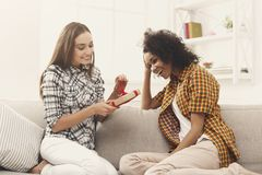 Excited woman getting gift from her girlfiend. Excited women getting gift from her girlfriend. Two happy female friends exchanging presents, copy space Stock Image