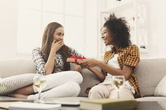 Excited woman getting gift from her girlfiend. Excited women getting gift from her girlfriend. Two happy female friends exchanging presents, copy space Royalty Free Stock Photo