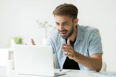 Excited worker satisfied with successful investment. Excited casual happy male worker looking at laptop screen, gaining profit, satisfied with successful Stock Image