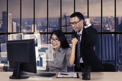 Excited workers with graph on monitor Stock Images