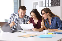 Excited workers reading a good results report. Three excited workers reading a good results report sitting in a desktop at office Royalty Free Stock Images