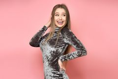 Excited young adult woman looking to the side smiling wearing elegant dress against pink wall. royalty free stock image