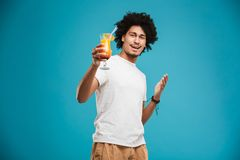 Excited young african curly man holding cocktail. Image of excited young african curly man standing isolated over blue background holding cocktail Royalty Free Stock Image