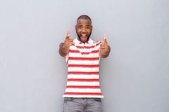 Excited young african man pointing. Portrait of excited young african man pointing at camera against gray wall royalty free stock photo