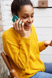 Excited young african woman at cafe talking on mobile phone Stock Image