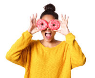 Excited young african woman covering her eyes with donuts. Close up portrait of excited young african woman covering her eyes with donuts on white background Royalty Free Stock Photos