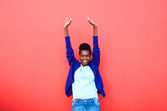 Excited young african woman standing with her arms raised