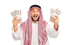 Excited young Arab holding few stacks of money Royalty Free Stock Photography