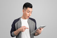 Excited young asian businessman holding digital tablet and point Stock Photo