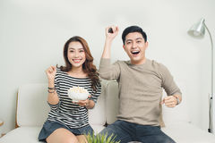 Excited young asian couple watching TV and eating popcorn Royalty Free Stock Photos