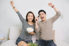 Excited young asian couple watching TV and eating popcorn Royalty Free Stock Image