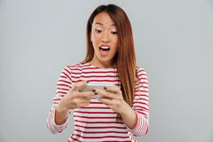 Excited young asian lady play games by phone Royalty Free Stock Image